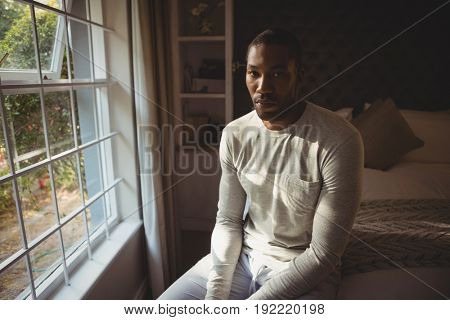 Portrait of serious man sitting on bed by window at home