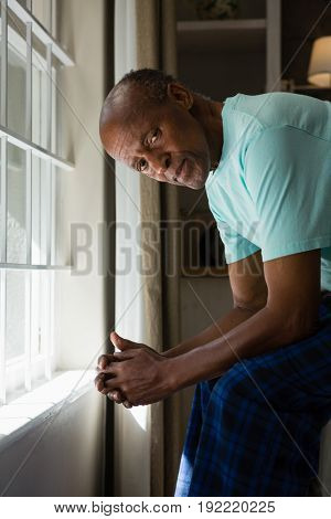 Portrait of serious senior man sitting by window at home