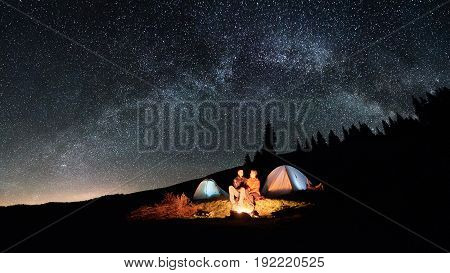 Night Camping. Couple Tourists Sitting At A Campfire Near Two Illuminated Tents Under Beautiful Nigh