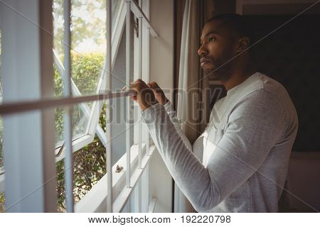 Side view of thoughtful man looking out through window while standing at home