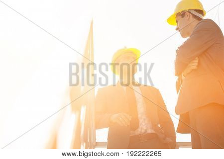 Low angle view of young male architect having discussion on stairway against clear sky