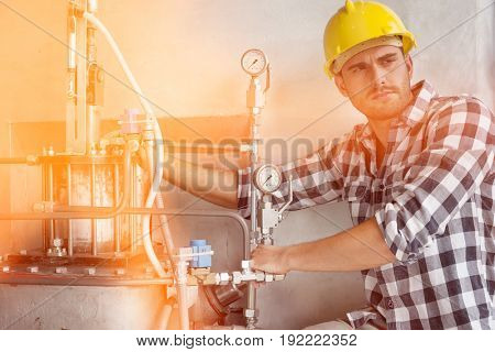 Young male worker examining machine in industry