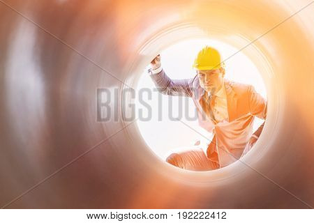 Young male supervisor examining large pipe at construction site