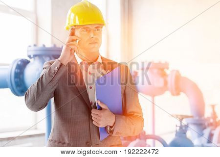 Young male manager with clipboard using cell phone in industry