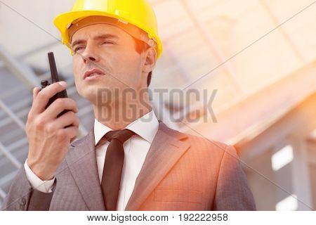Young male architect talking on two-way radio outdoors