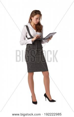 The attractive young woman stands with the laptop on a white background.
