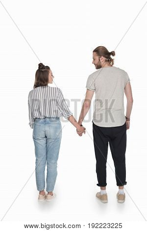 young caucasian couple holding hands and looking at each other isolated on white
