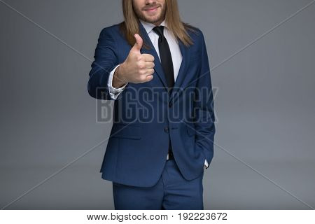 Cropped shot of handsome young man in suit showing thumb up sign
