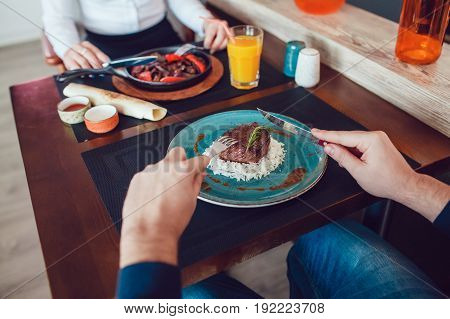 Man and woman are eating at the table. Only hands.