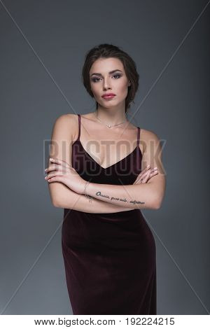 Young Caucasian Woman In Evening Dress Looking At Camera With Arms Crossed