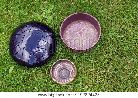 Singing Bowls And Steel Tongue Drum On The Grass Top View