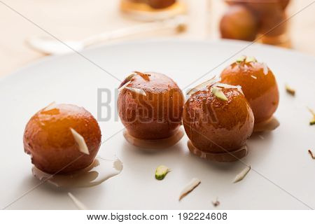 Indian Sweet food called Gulab Jamun made up of milk and sugar, a popular dish in festival or special occasion. Selective focus poster