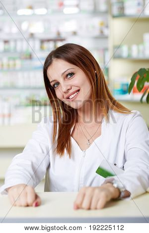 Young woman pharmacist at her desk with drug shelves in background