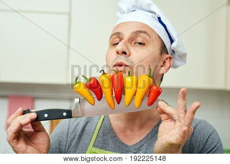 Male chef holding colorful small pepperes on his knife