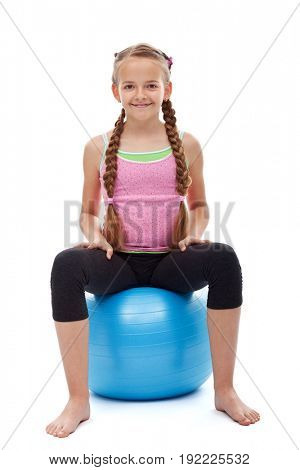 Happy young sporty girl sitting on large gymnastic rubber ball - smiling and relaxing, isolated