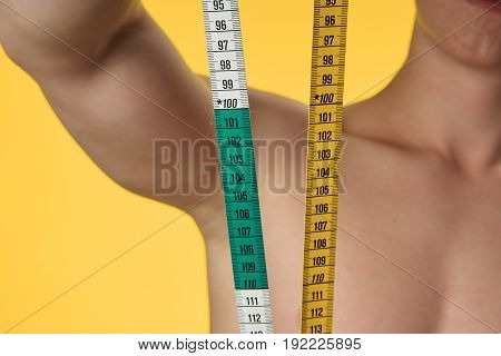 Man, losing weight, man holding a tape to measure his waist, a man on a yellow background.