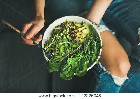 Green vegan breakfast meal in bowl with spinach, arugula, avocado, seeds and sprouts. Girl in jeans holding fork with knees and hands visible, top view, copy space. Clean eating, dieting food concept