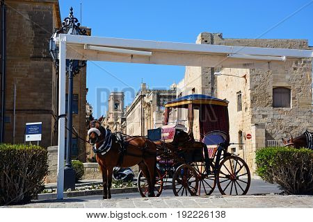 VALLETTA, MALTA - MARCH 30, 2017 - Horse drawn carriage by the Public Registry building Valletta Malta Europe, March 30, 2017.