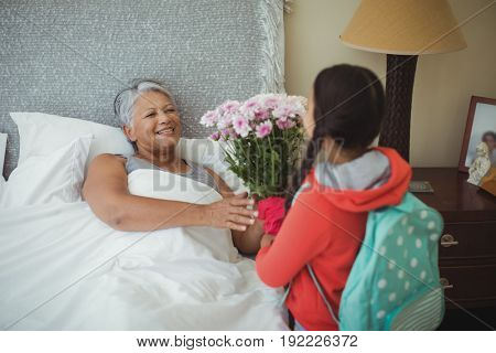 Granddaughter giving flowers to grandmother in bed room at home