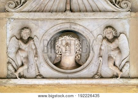 ROME, ITALY - SEPTEMBER 03: Young man of the Colonna family, flanked by a pair of cupids with downturned torches, bass relief in portico of church dei Santi XII Apostoli in Rome on September 03, 2016.