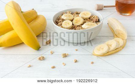 Granola muesli with fresh bananas and honey on white wooden background.