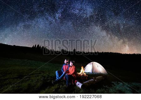 Night Camping. Man And Woman Tourists Have A Rest At A Campfire Near Illuminated Tent Under Beautifu