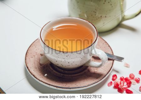 Cup of fruit tea on white table.