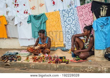 Hell-Ville Madagascar - December 19 2015: Indigenous women sell colorful embroidered tablecloths fabrics and souvenirs on the road at the Hell-Ville (Andoany) Nosy Be Island Madagascar.