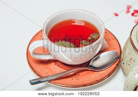 Cup of hot fruit tea on white table with mint.