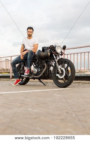 Rider man with beard and mustache in red sneakers sit on classic style biker cafe racer motorcycle with black glasses and look camera. Bike custom made in vintage garage. Brutal fun urban lifestyle.