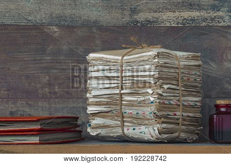 A stack of old letters and two red photo albums lie on the table