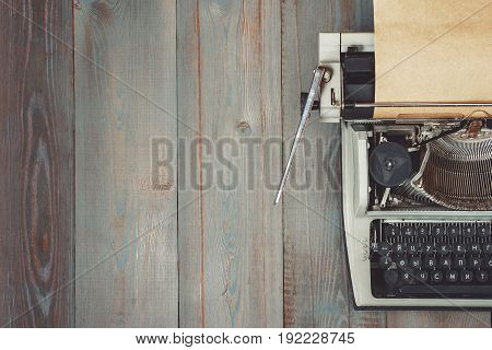 Fragment of an old typewriter with paper standing on a wooden table