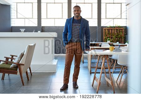 Portrait of a confident young African businessman in a blazer smiling while standing alone by a desk in a large modern office