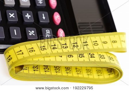 Tape for measurement in yellow color with plastic calculator in close up isolated on white background. Diet and calories counting concept