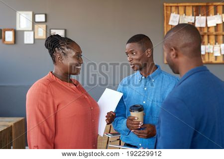 Three casually dressed young African work colleagues drinking coffee and talking together while having a break in a large modern office