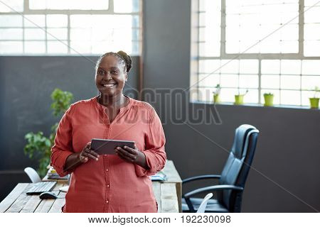 Portrait of a casually dressed young African businesswoman smiling and using a digital tablet while standing alone in a modern office