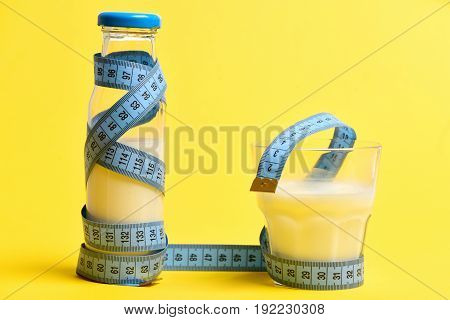 Concept of healthy dieting with bottle and glass of milk both wrapped with blue sewing centimeter isolated on yellow background