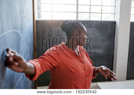 Focused and confident young African businesswoman giving a presentation to unseen colleagues while writing on a chalkboard in a modern office