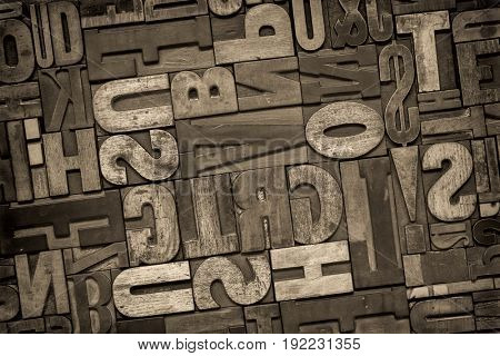 antique letterpress printing blocks, random collection of different size and style, black and white, sepia toned image