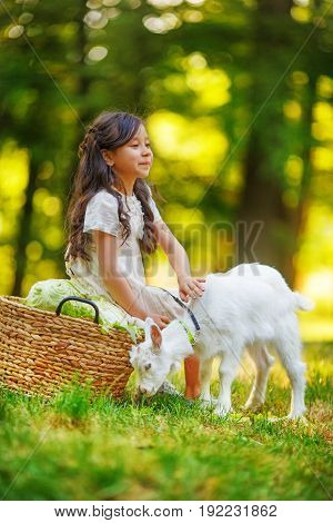A girl in a white dress grazes her little kid sitting on the edge of a forest near a wicker basket
