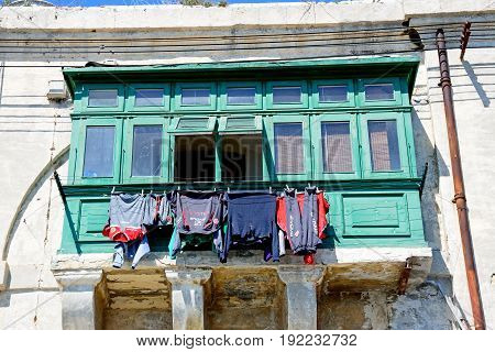 VALLETTA, MALTA - MARCH 30, 2017 - Traditional waterfront buildings with wooden windows and a washing line Valletta Malta Europe, March 30, 2017.