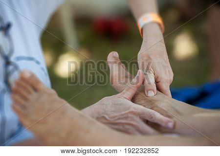 The massage therapist during a session of plantar reflexology