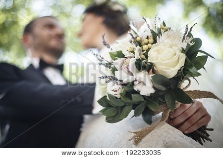 Bride and Groom Holding Beautiful, White Bridal Bouquet