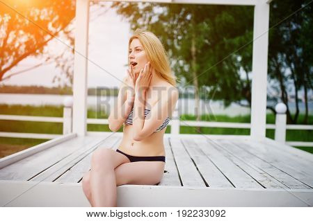 Portrait Of A Fabulous Young Woman In Bikini Sitting And Posing On A White Wooden Gazebo In The Park