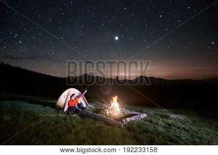 Night Camping In The Mountains. Couple Tourists Sitting In The Illuminated Tent Near Campfire, Looki