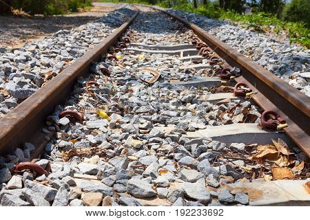 Old railroad with stones and leaves close up