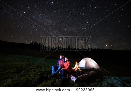 Night Camping. Man And Woman Tourists Have A Rest At A Campfire Near Illuminated Tent Under Starry S