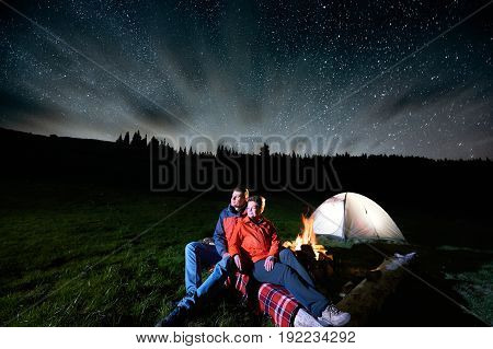 Night Camping In The Mountains. Romantic Couple Tourists Sitting At A Campfire Near Illuminated Tent