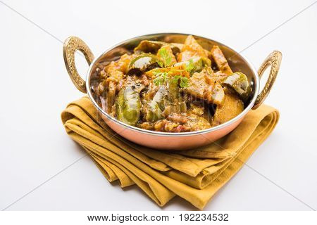 Indian baingan or baigan and aalu sabzi / Aloo Baingan Recipe / indian spicy eggplant and potato curry, served in kadhai or white bowl, selective focus