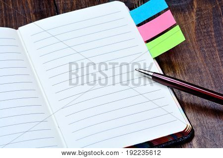 Empty notepad with pen on wooden table
